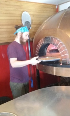 Dan Pizzutillo places pumpkin seeds at the edge of the oven at Nomad Pizza for a quick roast.